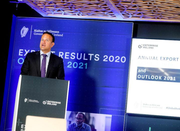 Leo Varadkar stands in a suit at a podium, in front of a sign that says 'Enterprise Ireland export results 2020'.