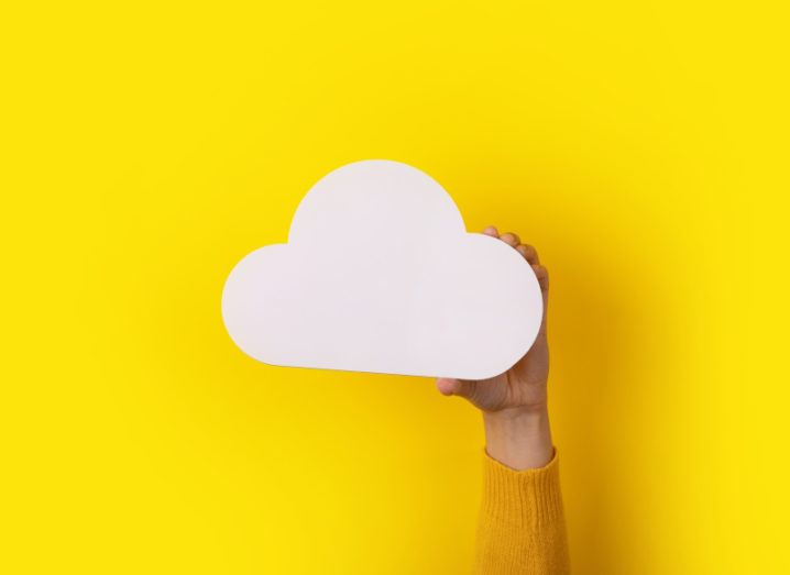 A person holds up a white cloud shape against a yellow background to symbolise the cloud experience.