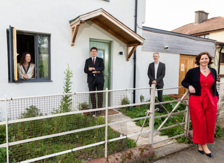 Two men and a woman stand outside a small house while another woman leans out a window. They are all smiling at the camera.