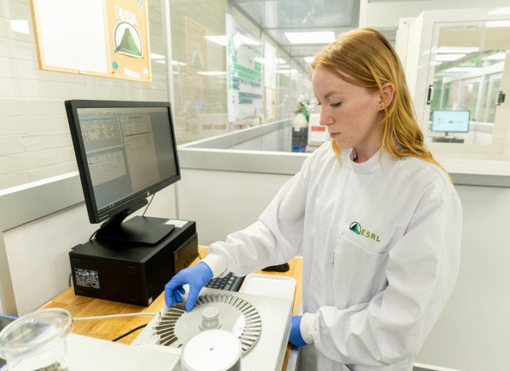 A scientist in a lab coat is working to analyse a soil and sediment sample in the new geological facility. They are placing soil samples into the analysis device, which is an off-white-coloured box and is connected to a computer monitor that is on the same desk.