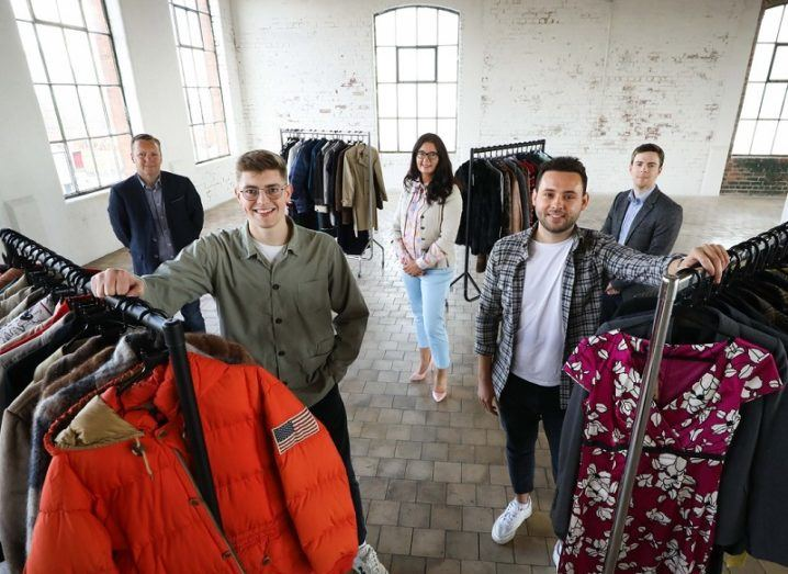 Five people stand in a warehouse-type room with rails of clothing surrounding them.