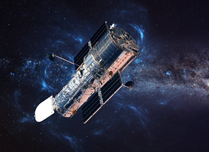 The Hubble telescope pictured orbiting in space. Its silver body stands out against darkness of space, with stars interspersed in the distance.