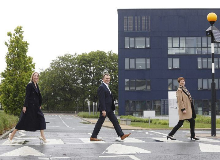 Three people walk across a zebra crossing in front of the large, blue IADT Media Cube building.