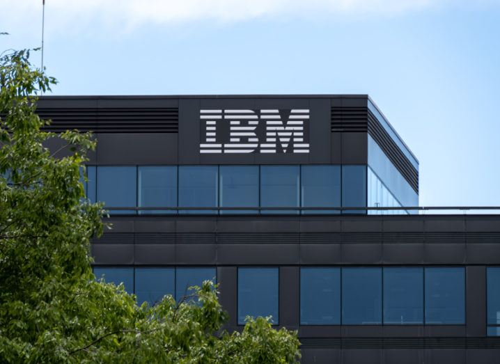 An IBM logo at the top of a large office building against a blue sky. There's a leafy tree to the left of the building.