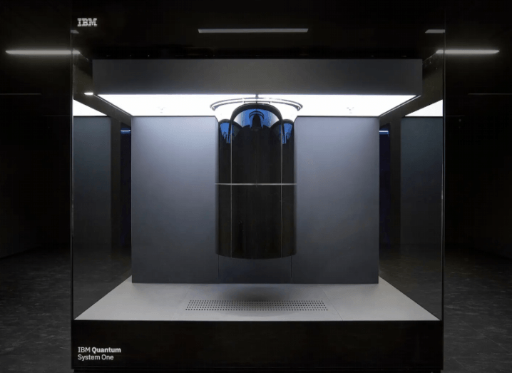 A large glass-panelled container surrounds a quantum computing system in a darkened room.