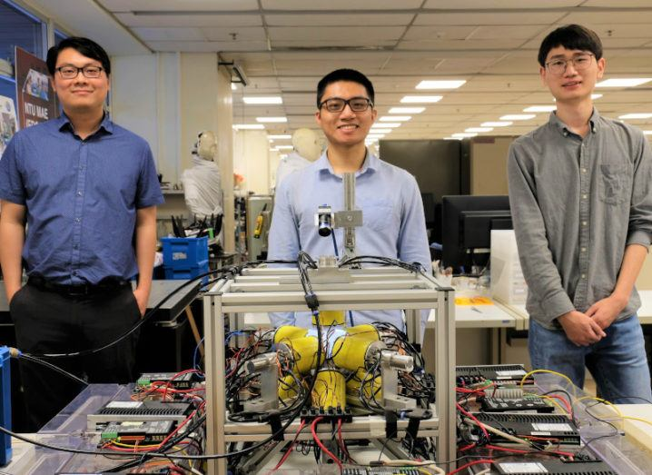 Researchers Lum Guo Zhan, Yang Zilin and Xu Changyu pose with the electromagnetic coil system used to generate the magnetic fields to control the mini robots.