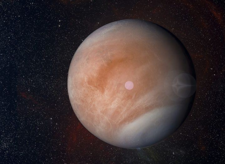 The orange-brown Venus is pictured in space. Stars can be seen faintly in the background.