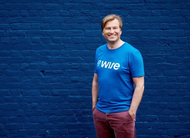 A man in a blue T-shirt that says Wise stands in front of a blue brick wall.