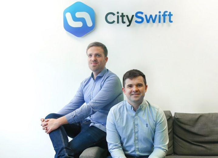 Two men are sitting on a couch beneath a sign that says 'CitySwift'.