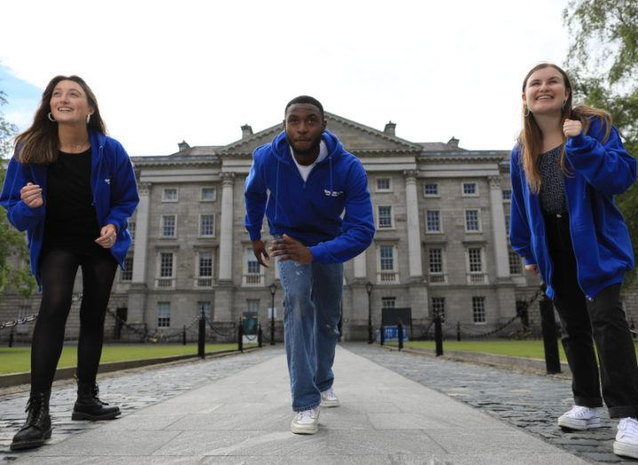 Three student entrepreneurs in matching blue hoodies pose on the Trinity campus as if they are about to start a race.