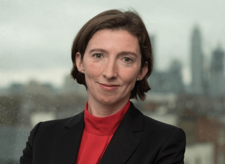 UK NCSC CEO Lindy Cameron poses in front of a window looking out on a dreary cityscape.