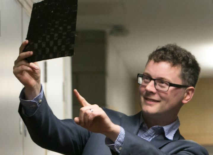 Bernal Institute researcher Dr Maurice Collins holds up a dark square sample of the carbon fibre material he has helped to develop.