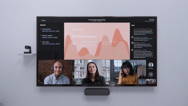 Un grand écran montrant Microsoft Teams avec sa nouvelle fonctionnalité de première ligne avec trois écrans d'employés distants en bas.