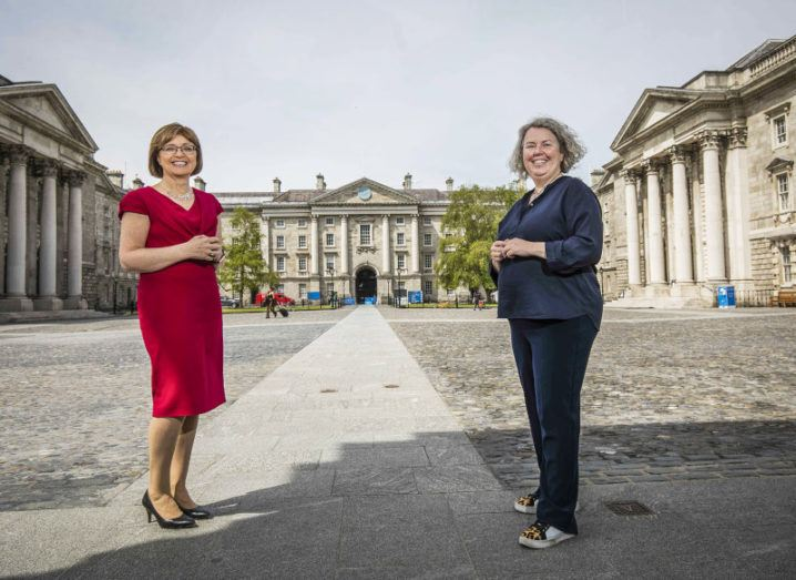 Two women stand socially distanced in the front square of Trinity College Dublin.