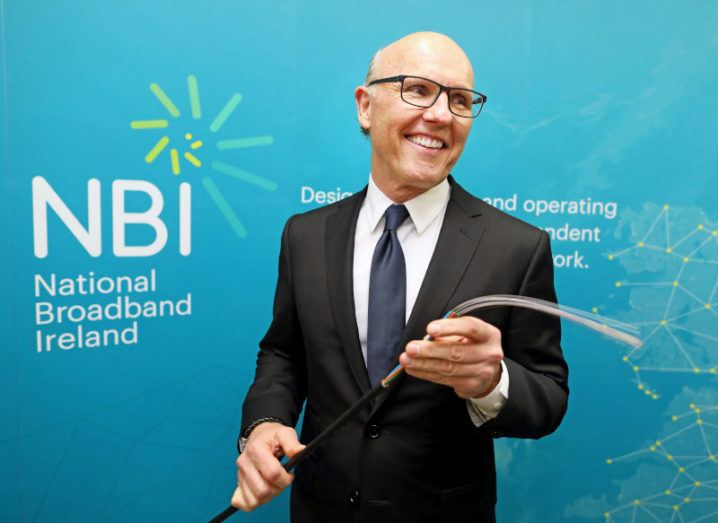 David McCourt stands in a suit, holding a fibre cable, in front of a sign that says National Broadband Ireland.