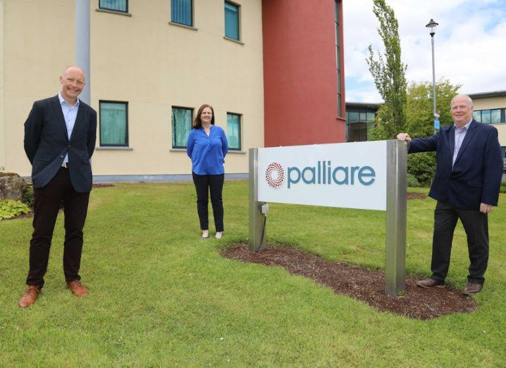 John O'Dea, Caroline O'Dea, and Tomás Ó Síocháin stand beside a Palliare sign. They are smiling and standing on grass with two metres between them.