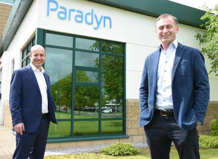 Two men in business suits stand a few metres apart outside an office building with a blue Paradyn logo at the top.