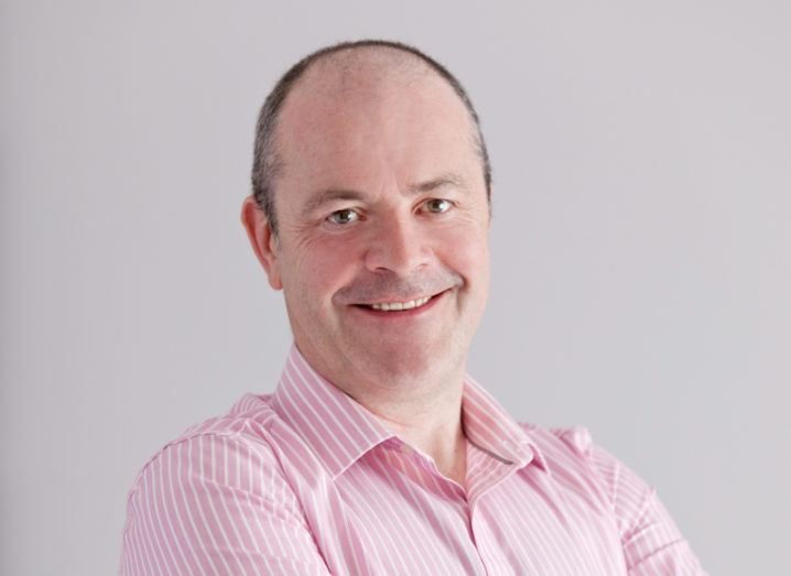 A headshot of Paul Meehan of HPE in a pink shirt, smiling at the camera against a grey background.