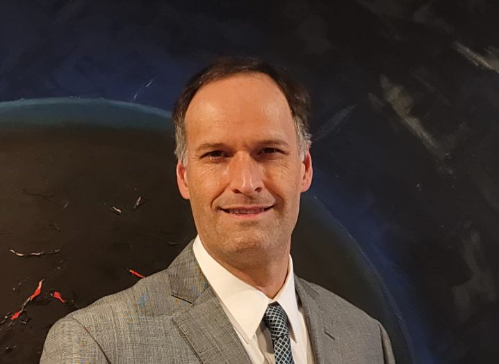 A man in a grey suit and patterned tie pictured against an abstract painting of a planet in space.