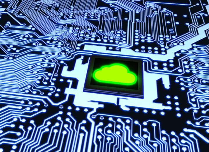 A blue-lit computing circuit board, with a green cloud shape on the microchip at the centre, representing quantum cloud computing.