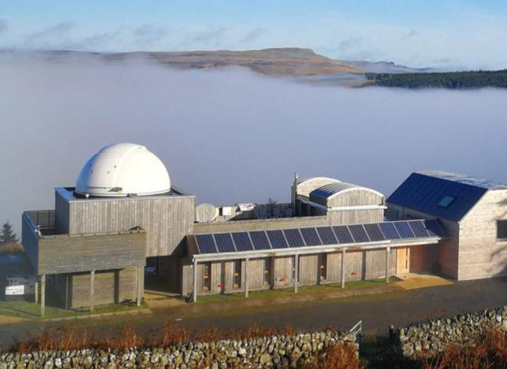 The Scottish Dark Sky Observatory viewed from a height, encircled by a low-lying cloud in Galloway Forest Park.
