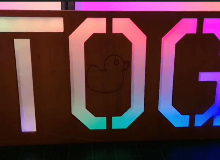 A sign that spells out Tog in large letters, lit up by multicoloured lights.