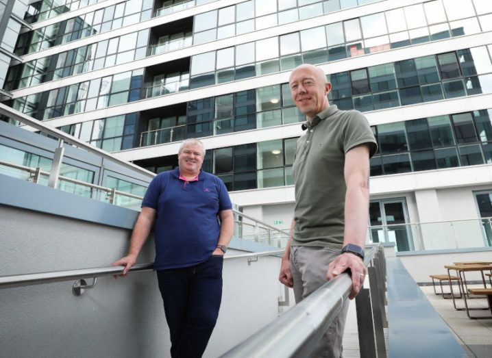 Neueda CEO Paddy O'Hagan and Version 1 CEO Tom O'Connor stand on a stairway in a courtyard outside a glass-panelled building.