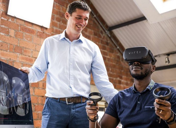 A man in business clothes is standing behind another man who is wearing a virtual reality headset.