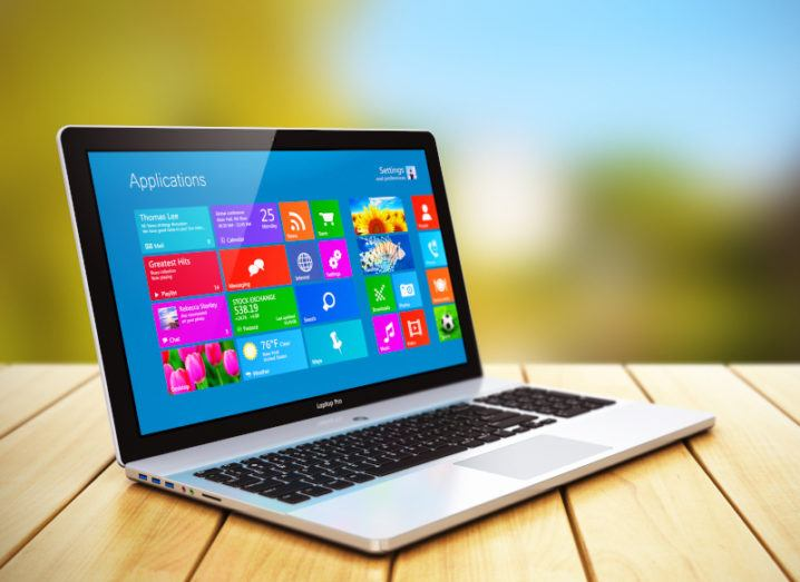 A laptop sitting on a wooden desk against a bright outdoor blurred background. A Microsoft Windows operating system is on the screen.