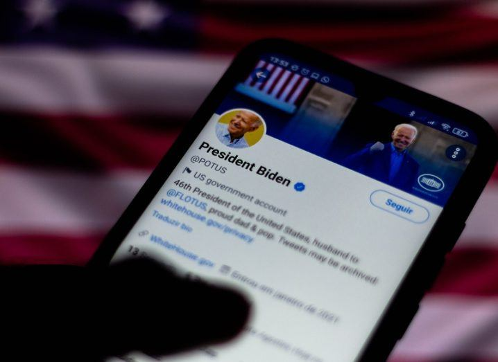 A person's hand is holding a smartphone that has Joe Biden's Twitter page open on the screen.