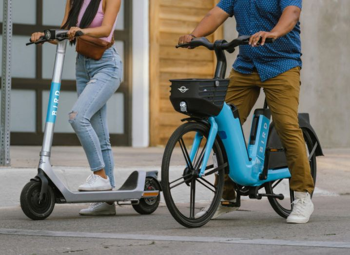 Two people are pictured on the street. A woman is on the left, standing on a Bird brand electric scooter. A man is to her right, seated on a Bird brand electric bike.