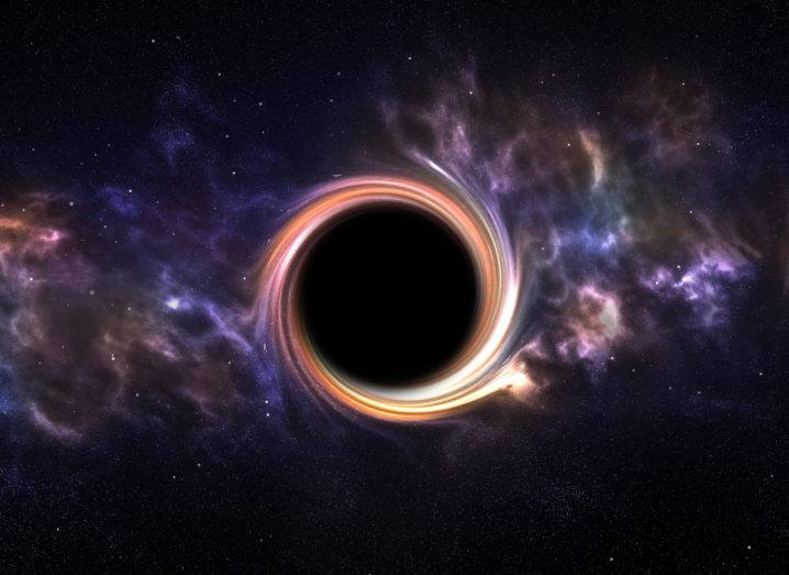 A black hole is pictured in space. The centre is completely black with an orange outline. Space appears purple beside the darkness of the hole, with stars in the background.