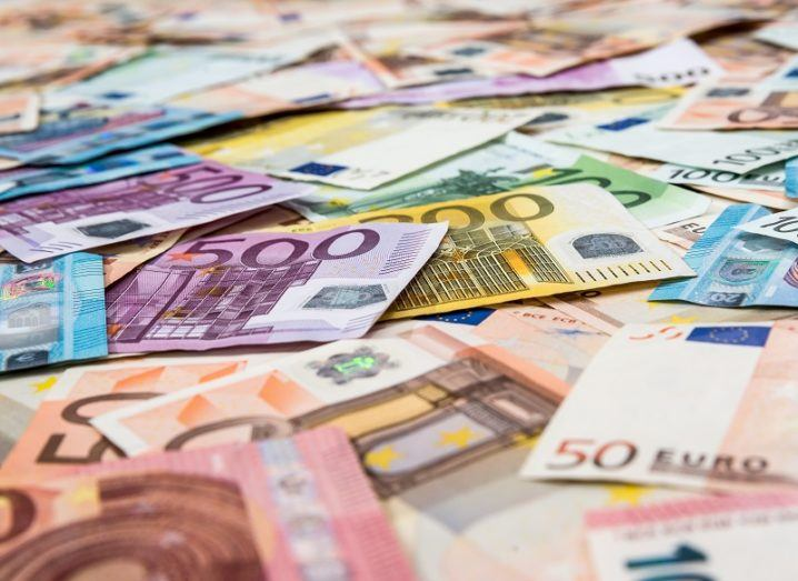 A pile of euro notes are spread out across a surface.