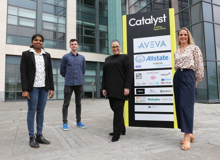 Four people stand outside beside a sign for the Catalyst hub.