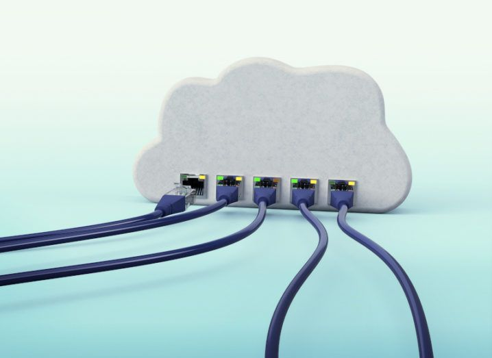 A cloud-native architecture concept. Several wires are plugged into the bottom of a 3D white cloud on a turquoise surface.