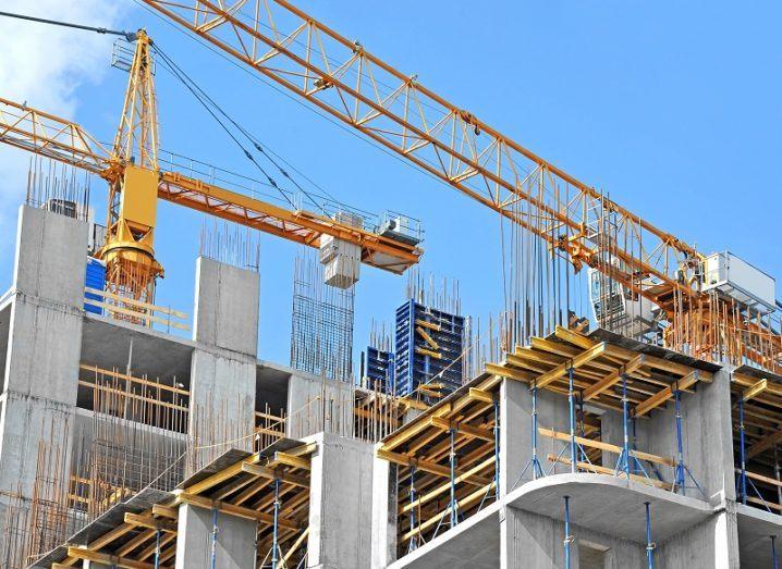 Cranes and building construction set against a blue sky.
