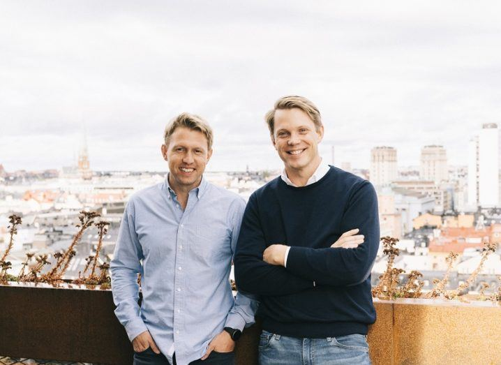 Two men stand on a rooftop with a city behind them.