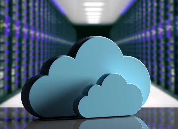A 3D blue cloud shape sits on a surface inside a large data centre server room.