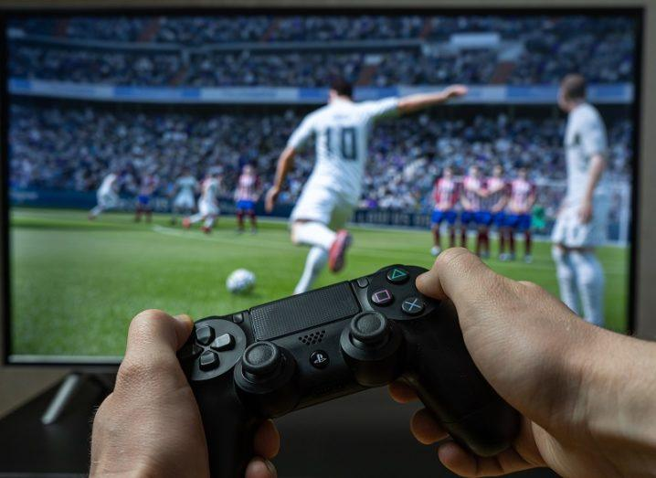 A person's hands are holding a gaming controller, in front of a screen that is displaying a football game.