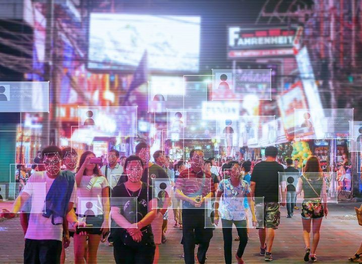 Image of a city street, with facial recognition technology highlighting people's faces.
