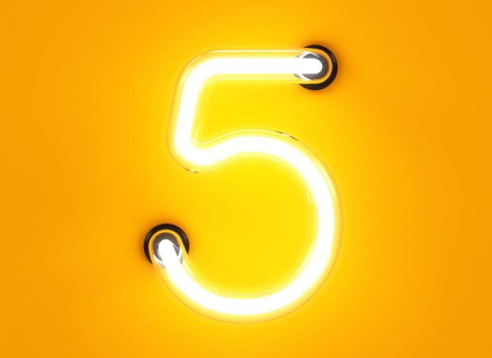 A thin orange neon number five sign against a bright orange background.