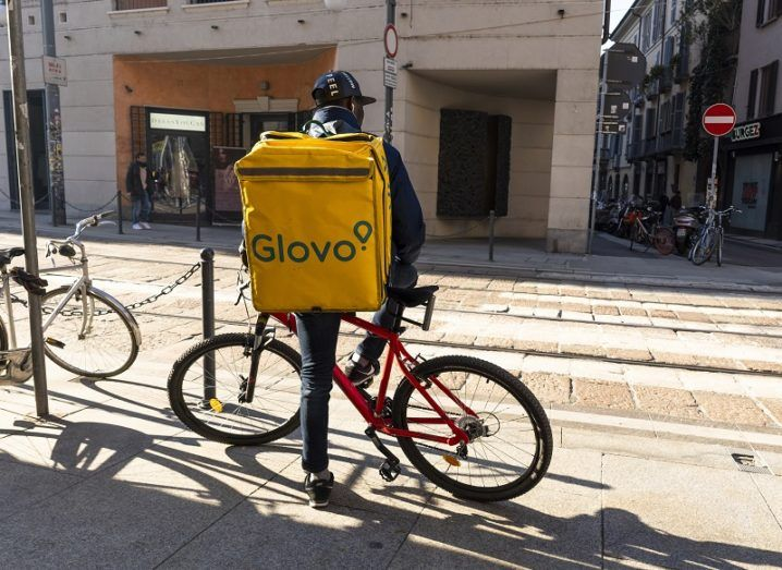 A Glovo delivery rider standing beside his bicycle on the street.