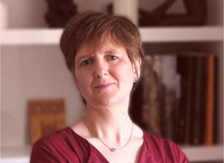 A woman with short hair wearing a dark red top smiles at the camera. In the background is an out-of-focus bookcase.