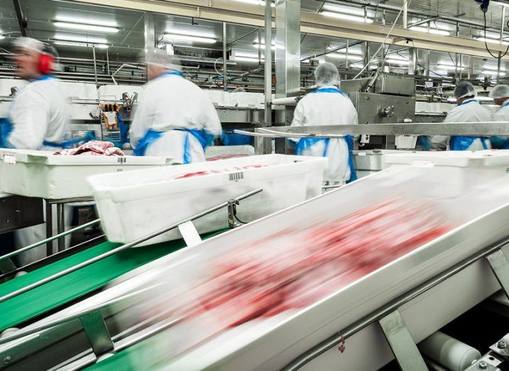 Meat whizzes down a production line in a factory, with workers in protective gear working in the background.