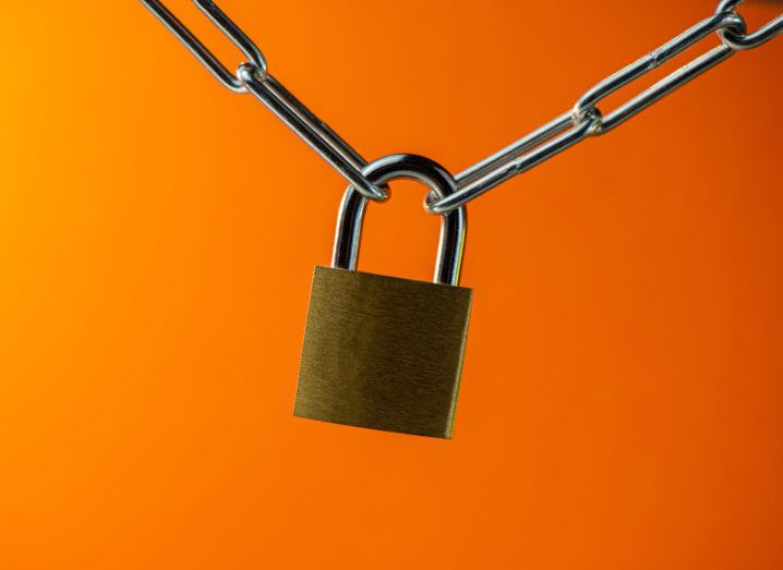 A padlock hangs from a chain against a bright orange background, symbolising cybersecurity.