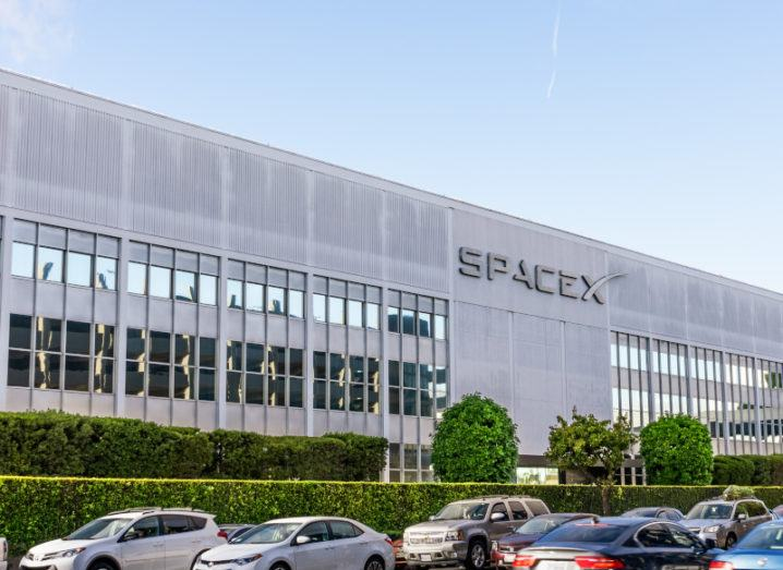The SpaceX building is pictured from the parking lot. Cars are visible in front of the building. The SpaceX logo is on the side, with windows built into the tall, grey walls.