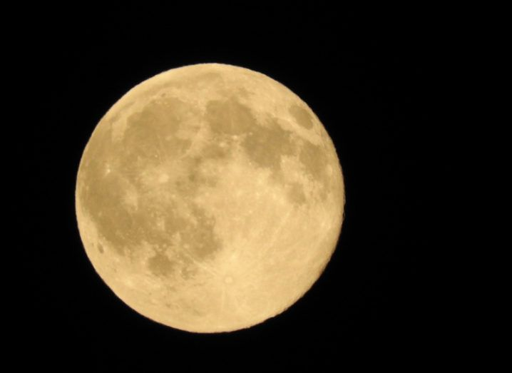 A picture of the yellow-tinted full moon in the night sky.