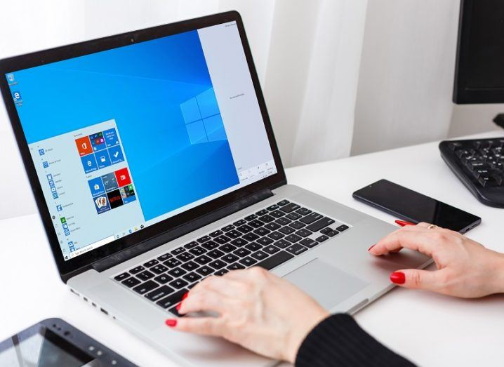 A woman's hands are using a laptop, which is running the Windows 10 operating system.