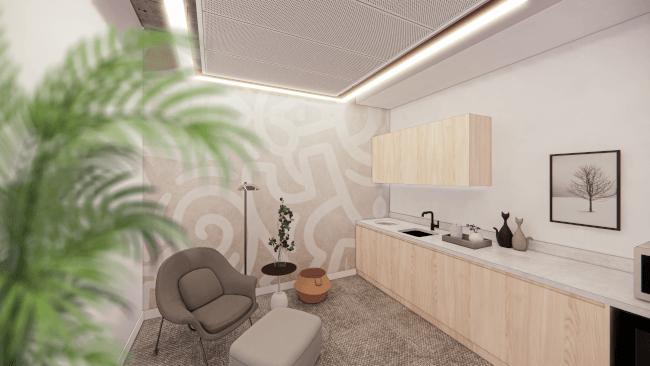 Une petite pièce chaleureusement éclairée avec une kitchenette, un petit fauteuil et un repose-pieds.
