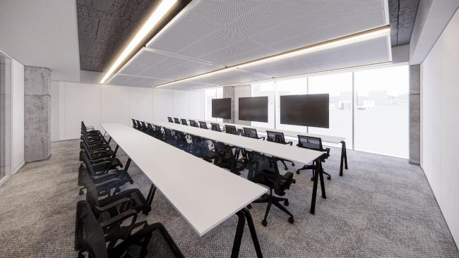 Une salle de formation avec trois longues tables avec de nombreux sièges devant trois grands écrans.